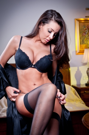 boudoir: attractive sexy brunette with black lingerie posing challenging  Portrait of sensual woman wearing black bra in classic boudoir scene  Long hair brunette wearing black boudoir outfit in vintage room