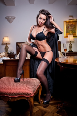 attractive sexy brunette with black lingerie posing challenging  Portrait of sensual woman wearing black bra in classic boudoir scene  Long hair brunette wearing black boudoir outfit in vintage room Stock Photo - 22251310