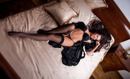 22988303: Beautiful and sexy brunette young woman wearing black lingerie in bed  Fashion shoot lingerie indoor  Sexy young girl in black lingerie in hotel  Stock Photo