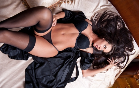 Beautiful and sexy brunette young woman wearing black lingerie in bed  Fashion shoot lingerie indoor  Sexy young girl in black lingerie in hotel  photo