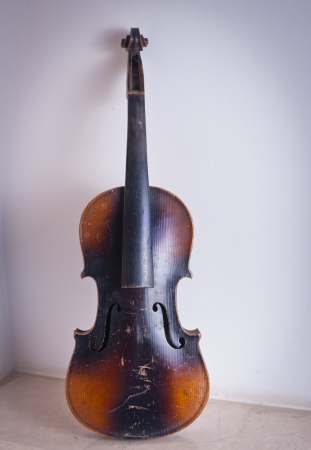 necking: old violin leaning against the wall Stock Photo