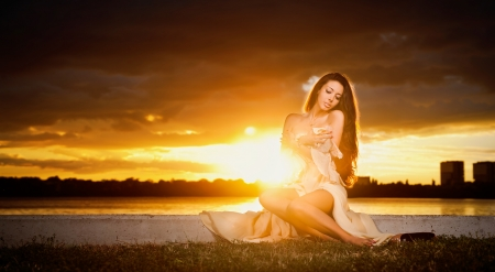 brunette caucasian woman in dress posing provocatively outdoor in front of a beautiful sunset   photo