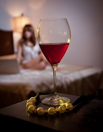 Mysterious lady staying in bed working on laptop with a glass of wine and a rope of golden pearls foreground  Sensual woman on bed and glass of wine  Beautiful girl indoor relaxation moments Stock Photo