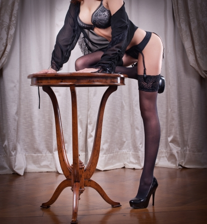 Sexy beautiful body shot of young woman wearing black lingerie and stockings Long legs in black stockings indoor Woman leading on a vintage table wearing black stockings and high heels photo