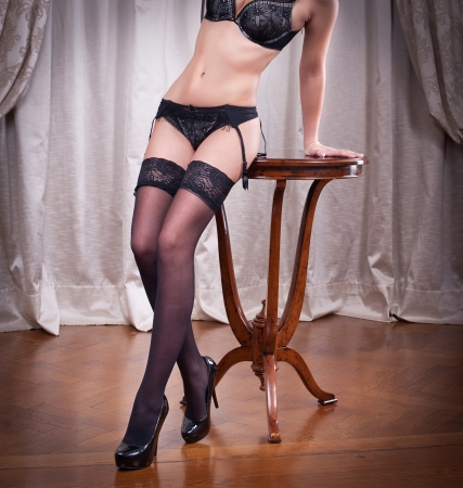 Sexy beautiful body shot of young woman wearing black lingerie and stockings Long legs in black stockings indoor Woman leading on a chair wearing black stockings and high heels photo