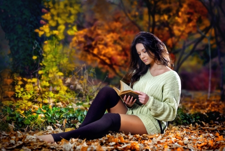Young caucasian sensual woman reading a book in a romantic autumn scenery  photo