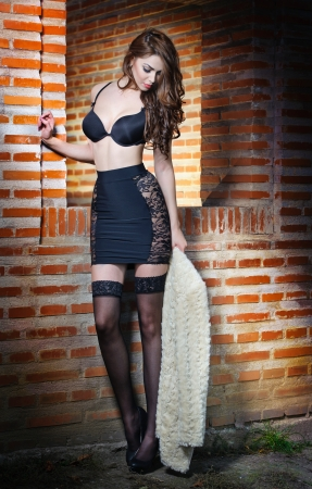 Beautiful brunette woman in black sensual lingerie posing provocatively in front of a brick wall  Young model wearing black stockings posing pretty  Caucasian model standing near red brick wall photo