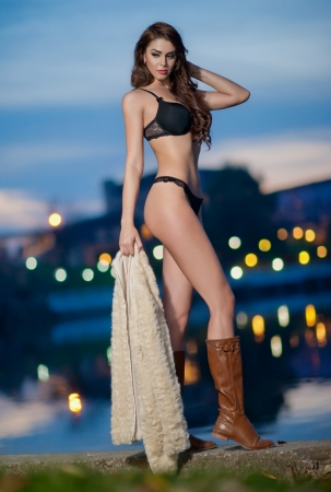 Young sexy girl on street at night  Beautiful brunette with long legs outdoor  Sensual woman wearing leather boots in night  Sexy fashionable model posing in night outdoor photo
