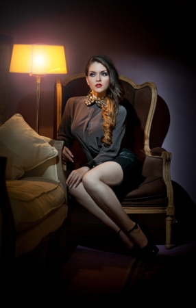Young beautiful luxurious woman sitting on a vintage couch  Beautiful young woman in a luxurious classic interior  Seductive woman in luxury manor, vintage style photo