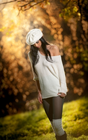 Beautiful sexy girl in white posing in park in autumn day  Beautiful elegant woman with white cap in autumn park  Young pretty brunette woman with leggings and long legs in the forest photo