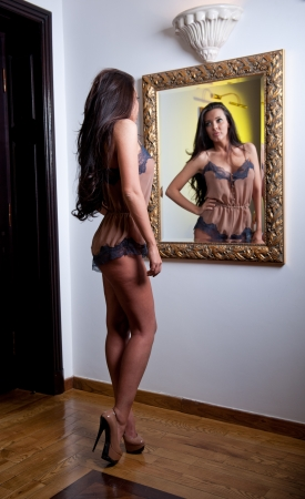 Sensual elegant woman in lingerie looking into mirror in a hotel  Beautiful and sexy brunette young woman wearing sexy lingerie posing near a vintage mirror  Fashionable model with black long hair photo