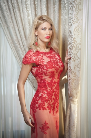 Young beautiful luxurious woman in long elegant dress  Beautiful young blonde woman in red dress with curtains in Seductive blonde woman with red lace dress in luxury manor, vintage style photo
