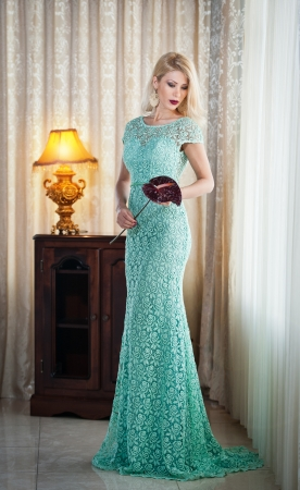 Young beautiful luxurious woman in long elegant dress  Beautiful young blonde woman in turquoise dress with curtains in Seductive blonde woman in lace dress in luxury manor, vintage style photo