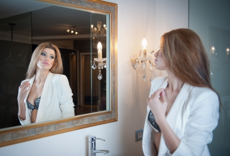 Sensual elegant woman in office outfit looking into a large mirror  Beautiful and sexy blonde young woman wearing an elegant white jacket posing in a mirror  Fashionable model  Standard-Bild