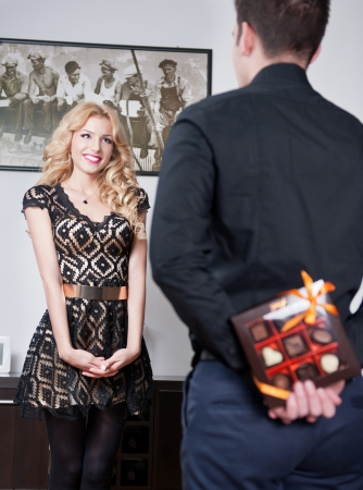 make a gift: Attractive blonde girl smiling and waiting a surprise from her boyfriend  Man hiding behind a candies box of girlfriend  Man holding a box of chocolate at his back to make a gift to his girlfriend  Stock Photo