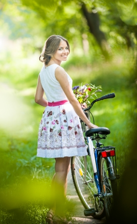 Beautiful girl wearing a nice white dress having fun in park with bicycle  Healthy outdoor lifestyle concept  Vintage scenery  Pretty blonde girl with retro look with bike and basket with flowers Standard-Bild