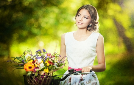 Beautiful girl wearing a nice white dress having fun in park with bicycle carrying a beautiful basket full of flowers  Vintage scenery  Pretty blonde girl with retro look, bike and basket with flowers photo