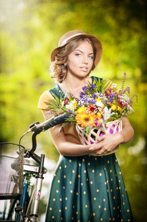 Beautiful girl with cute hat and basket with flowers having fun in park with bicycle  Healthy outdoor lifestyle concept  Vintage scenery  Pretty blonde girl with retro look with bike photo