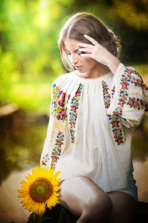 Young girl wearing Romanian traditional blouse holding a sunflower outdoor shot  Portrait of beautiful blonde girl with bright yellow flower  Beautiful woman looking at a flower harmony concept