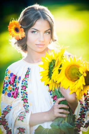 Young girl wearing Romanian traditional blouse holding sunflowers outdoor shot  Portrait of beautiful blonde girl with bright yellow flowers bouquet  Beautiful woman with yellow flower in hair posing Standard-Bild