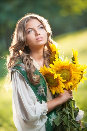 Young girl wearing Romanian traditional blouse holding sunflowers outdoor shot  Portrait of beautiful blonde girl with bright yellow flowers bouquet  Beautiful woman with long fair hair - fairy look