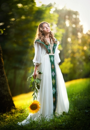 Young woman wearing a long white dress holding a sunflower outdoor shot  Portrait of beautiful blonde girl with bright yellow flower in forest  Attractive girl with long hair - fairy tale scenery photo