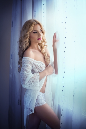 Attractive sexy blonde with white lace lingerie near the curtains looking on the window  Standard-Bild