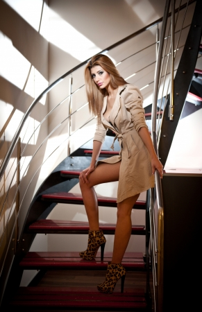 belle: Full-length portrait of blonde woman wearing a coat posing provocatively on steps in a modern interior  Beautiful woman in casual style coat and high heel shoes on stairs full body shoot indoor Stock Photo