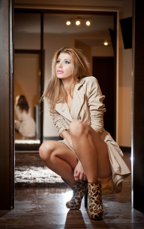 animal sexy: Portrait of blonde woman wearing a coat indoor  Beautiful young woman in coat posing in modern interior  Woman in casual style coat and high heels animal print boots thinking  Full body shoot indoor