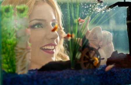 admiring: Beautiful blonde girl looking at golden fishes in aquarium  Attractive female with gorgeous smile admiring a large aquarium  Pretty woman playing with colored fishes swimming in aquarium Stock Photo