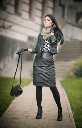 Attractive young woman in a winter fashion shot  Beautiful fashionable young girl in black leather waking on avenue  Elegant long hair brunette with handbag and scarf in urban scenery  photo