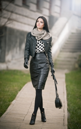 Attractive young woman in a winter fashion shot  Beautiful fashionable young girl in black leather waking on avenue  Elegant long hair brunette with handbag and scarf in urban scenery  Imagens