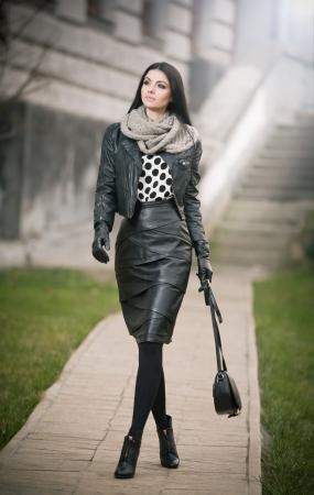 donne brune: Attraente giovane donna in una moda inverno shot Bella ragazza alla moda in pelle nera veglia sul viale elegante bruna capelli lunghi con la borsa e la sciarpa in paesaggio urbano
