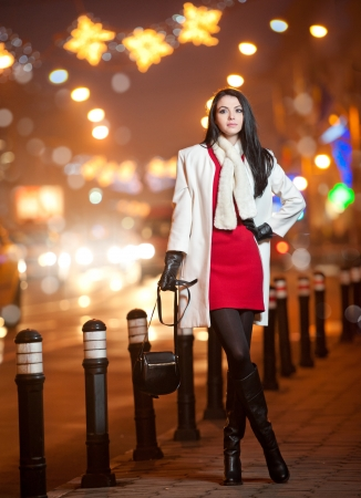Fashionable lady wearing red dress and white coat outdoor in urban scenery with city lights in background  Full length portrait of young beautiful elegant woman posing in winter style  Street shot