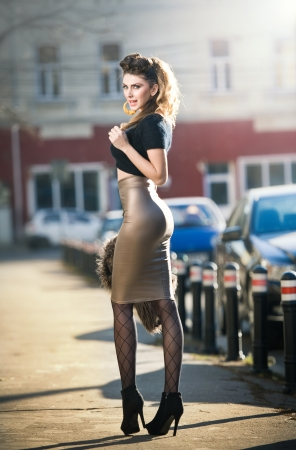 Attractive young woman in a urban fashion shot Beautiful fashionable young girl with tight-fitting clothes and long legs posing on the street Elegant blonde female posing in urban scenery