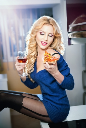 Attractive sexy blonde female with bright blue blouse and black stockings posing smiling eating a pizza slice and holding a glass with red wine  Portrait of sensual fair hair woman in modern scenery