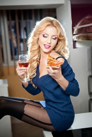 blusa: Atractivo sexy rubia mujer con blusa azul brillante y medias negras posando sonriente comer una rebanada de pizza y la celebración de un vaso de vino tinto Retrato de la mujer sensual de pelo rubio en el paisaje moderno Foto de archivo