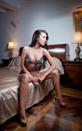 Beautiful and sexy brunette young woman wearing brown lingerie in bed  Fashion shoot lingerie indoor  Sexy young girl in black lingerie in a vintage scene photo