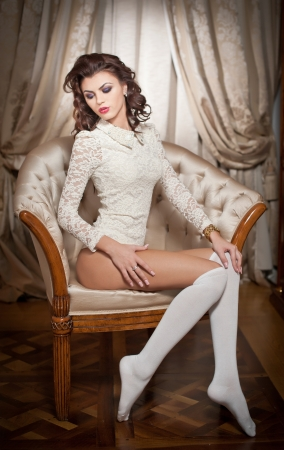 Beautiful young woman in white sitting on sofa posing provocatively in boudoir scenery  Attractive brunette girl with long hair and white long stockings laying down on vintage chair in bedroom photo