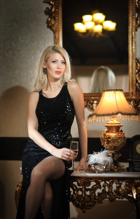 Young beautiful luxurious woman in long elegant black dress  Beautiful young blonde woman with bright lights in background  Seductive blonde woman in luxury manor, vintage style photo