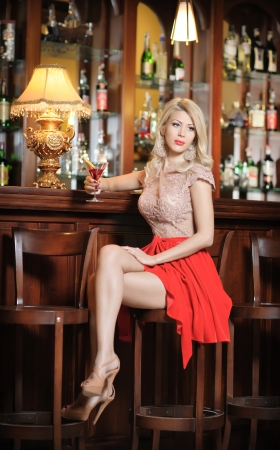 Attractive blonde woman with long hair in elegant nude and red dress sitting on bar stool  Gorgeous blonde model showing her long legs with high heels posing provocatively in vintage bar photo