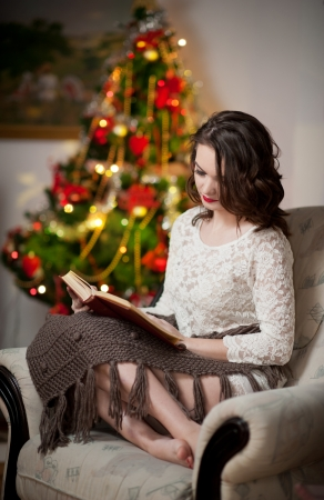 Beautiful sexy woman with Xmas tree in background reading a book sitting on chair  Portrait of a woman reading a book sitting comfortable with a blanket on legs  Attractive brunette female relaxing  photo