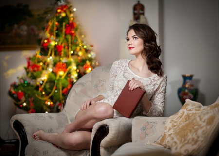 Beautiful sexy woman with Xmas tree in background reading a book sitting on chair  Portrait of a woman reading a book sitting comfortable  Attractive brunette female relaxing  photo