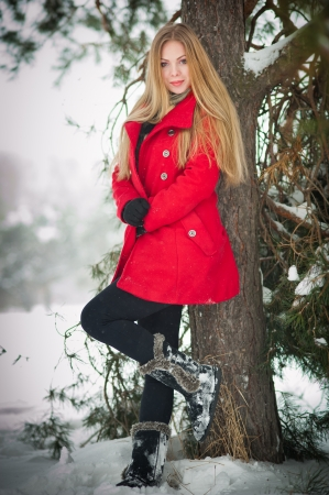 Attractive blonde girl with gloves and red coat posing winter snow Beautiful woman in the winter scenery  Young woman in wintertime outdoor photo