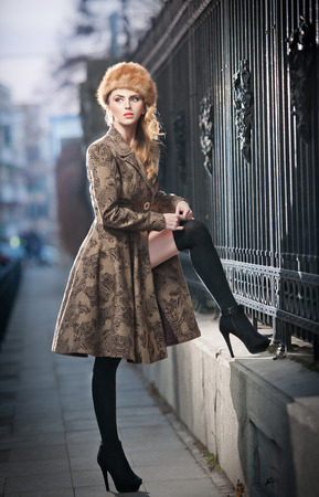 Attractive elegant blonde young woman wearing an outfit with Russian influence in urban fashion shot  Beautiful fashionable young girl with long legs and fur cap posing on street