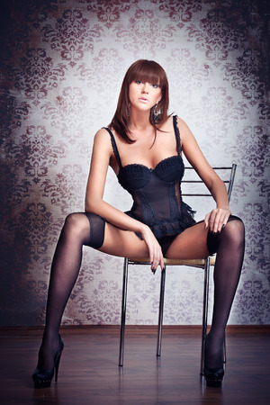 Attractive red hair model with black corset sitting provocatively on chair - gray background  Fashion portrait of a sensual woman - studio shot  Beautiful redhead female in black posing provocatively