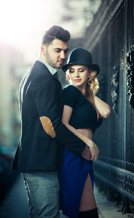 Couple in love in railway station  Beautiful well-dressed couple standing on railway platform  Handsome brunette young man holding a fashionable blonde with hat next to a train photo