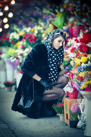 Beautiful brunette woman with gloves choosing flowers at the florist shop  photo