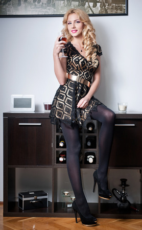 Attractive sexy blonde female wearing black dress with golden belt smiling holding a glass with red wine   Stock Photo