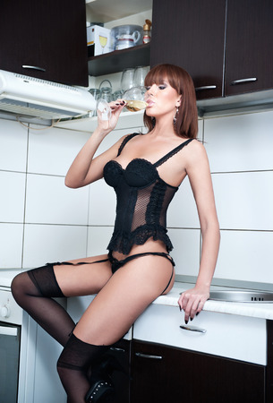 Attractive sexy red hair female with black lingerie and stockings drinking wine in a modern kitchen  Portrait of sensual redhead with black corset and long legs in modern scenery - indoor shot